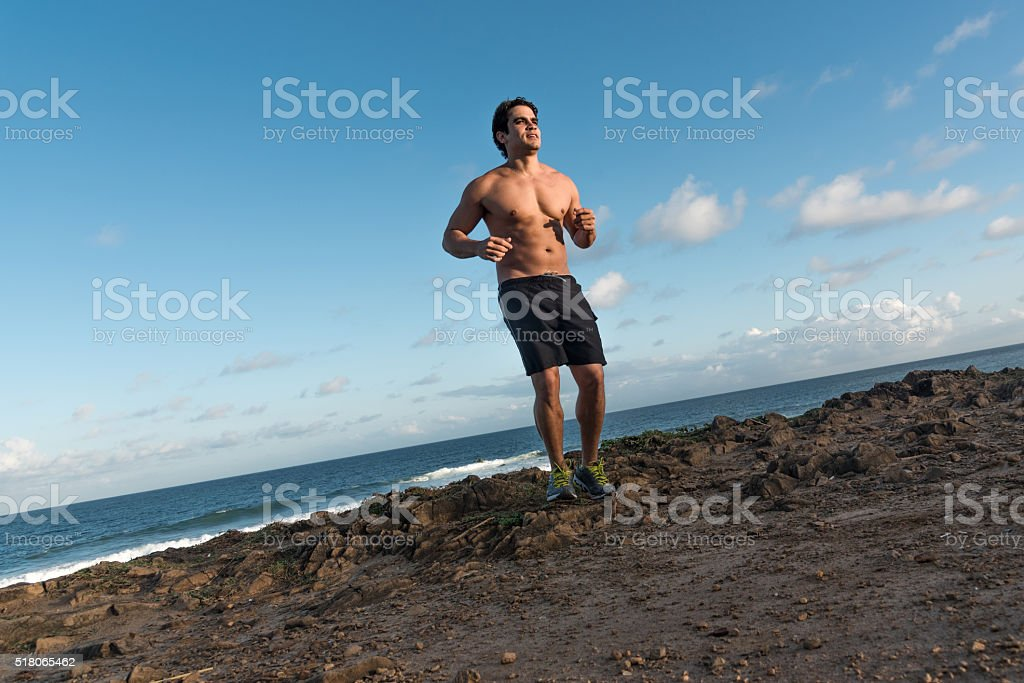 bare chested  latin sportsman jogging at tropic beach stock photo