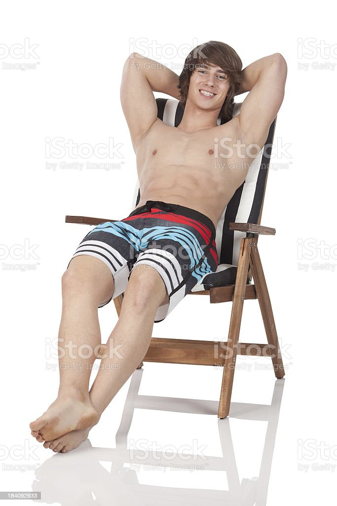 Bare chested man resting on a beach chair royalty-free stock photo