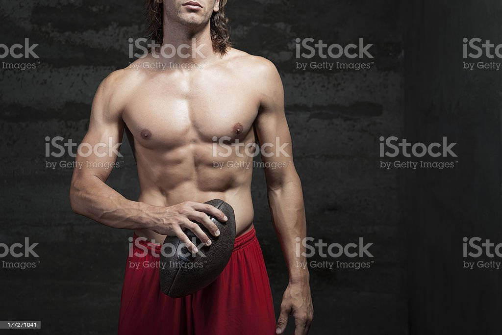 bare chested muscle man is holding football ball in hand royalty-free stock photo