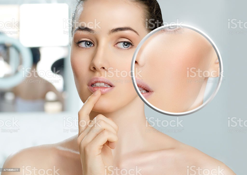 Bare faced woman looking closely at her face in a mirror stock photo