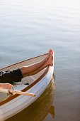 Bare feet in rowboat on lake