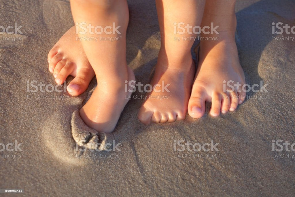 Bare feet in wet sand on beach stock photo