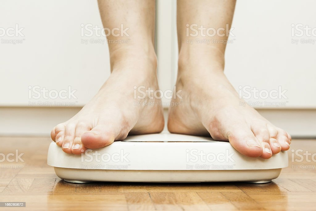 Bare feet standing on scales on a laminated floor stock photo