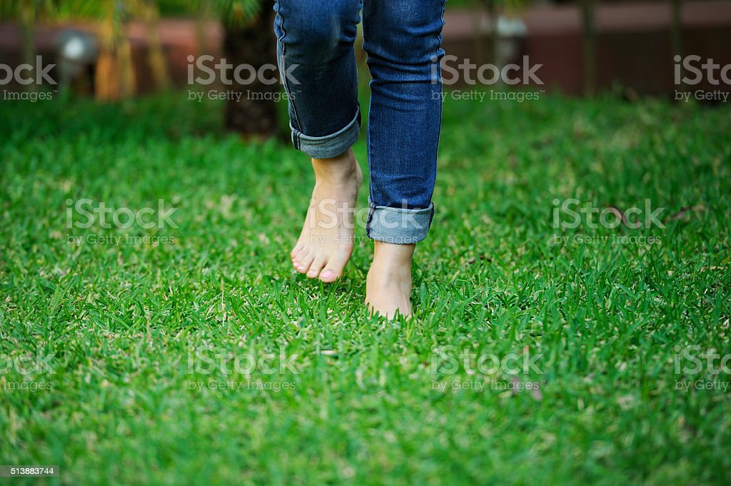 bare foot walking in grass stock photo