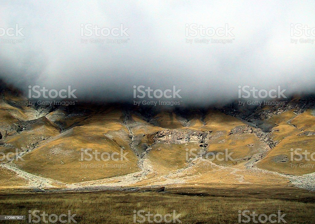 Bare hill with hanging cloud royalty-free stock photo