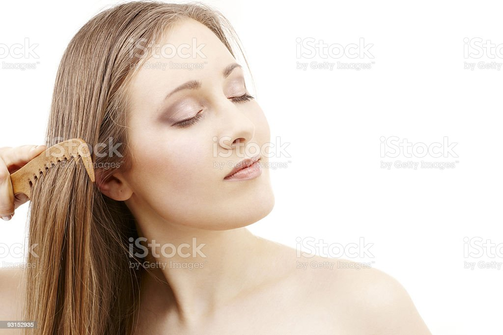 Bare shouldered woman with her eyes closed brushing her hair royalty-free stock photo