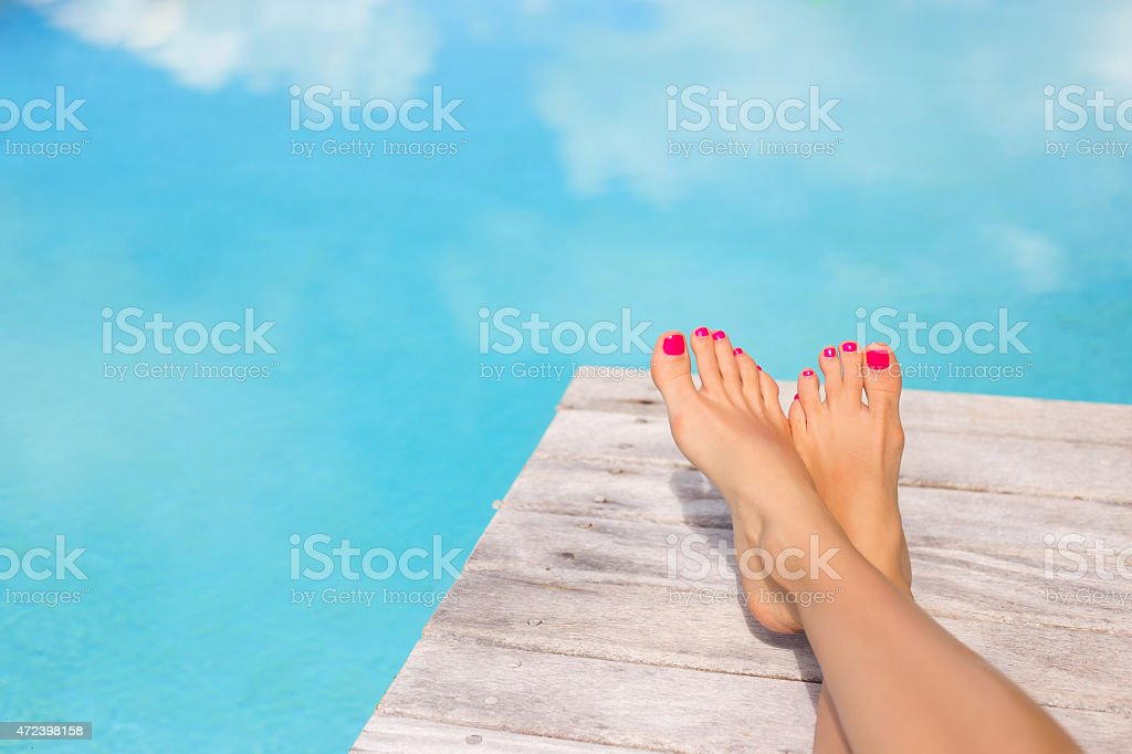 Bare woman feet by the swimming pool stock photo