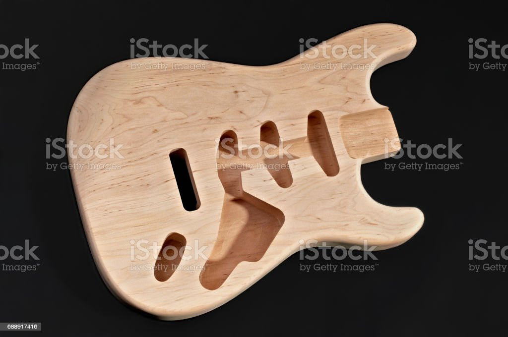 Bare wood or unfinished electric guitar body wood, with blank body plank beneath, Solid body guitar making stock photo