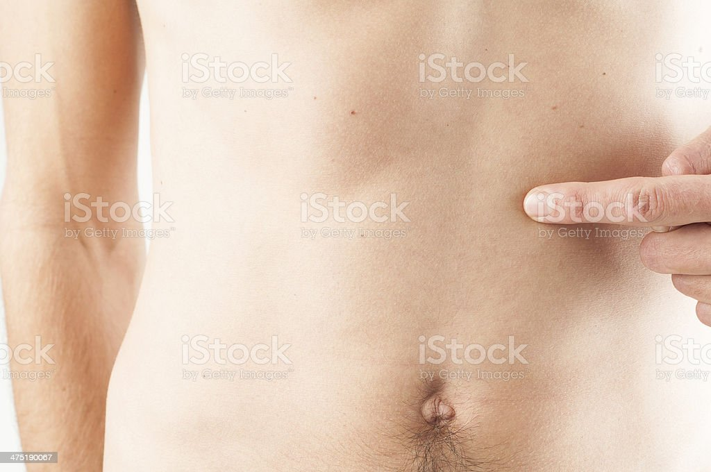 bare-chested patient pointing on his stomach where he feels pain stock photo