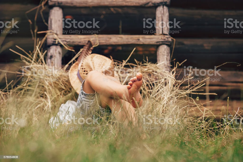 Barefoot boy sleeps on the grass near ladder in haystack stock photo
