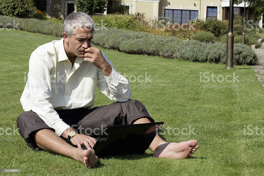 Barefoot businessman sitting on grass with laptop computer royalty-free stock photo