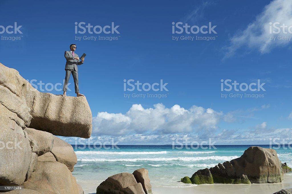 Barefoot Businessman Stands Using Tablet on Tropical Beach Rock royalty-free stock photo