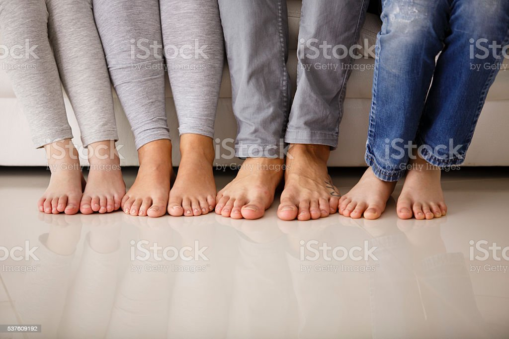 Barefoot family sitting on sofa, low section stock photo