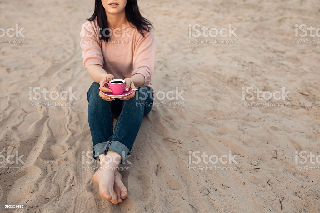 barefoot female on the beach and with cup of coffee; stock photo