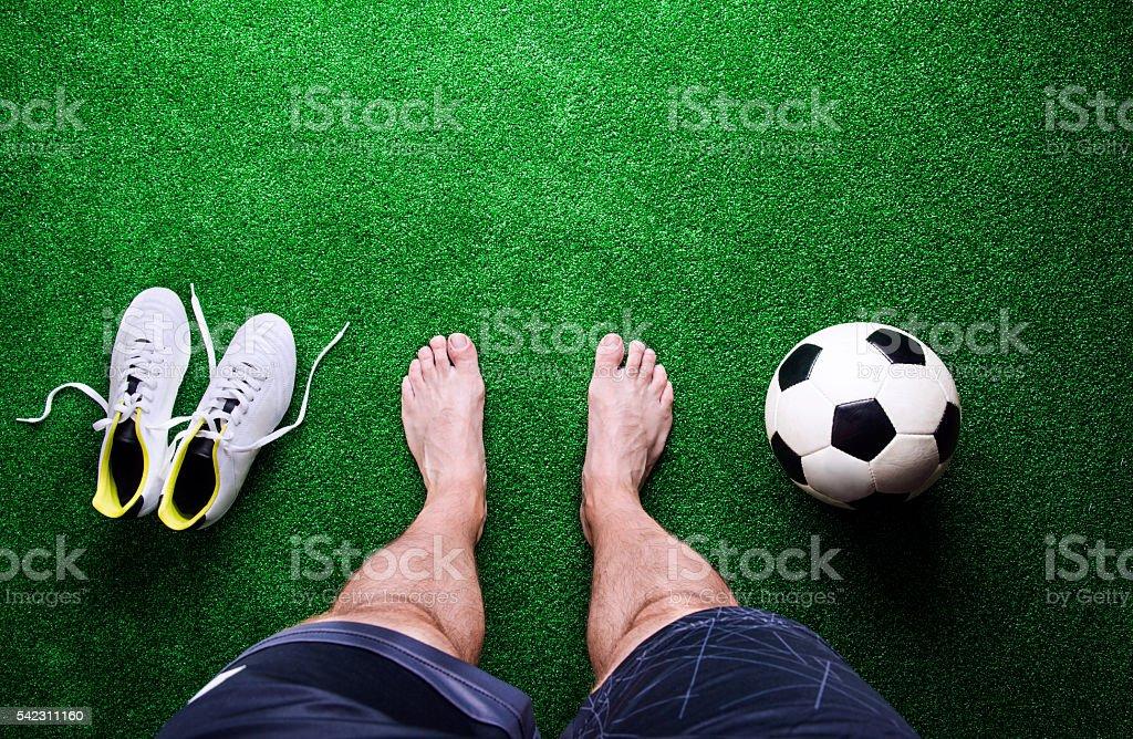 Barefoot football player against green grass, studio shot stock photo