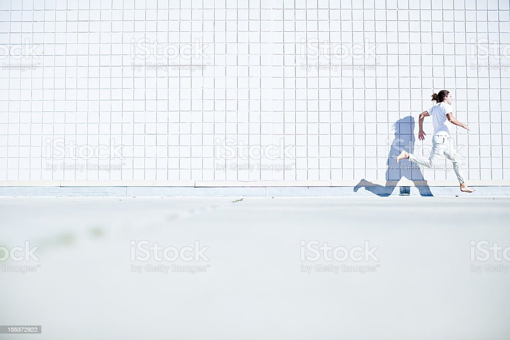 Barefoot free runner (parkour athlete) dressed all in white stock photo
