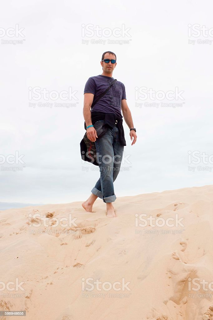 barefoot guy walking in the high of a dune stock photo