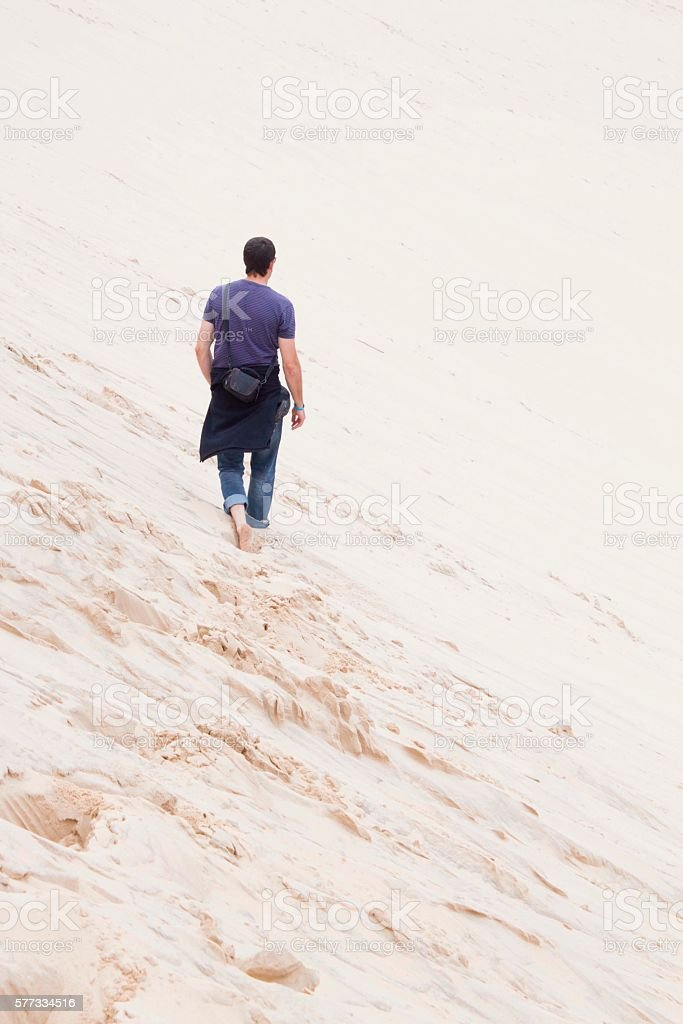 barefoot guy walking in the sand with his jeans stock photo