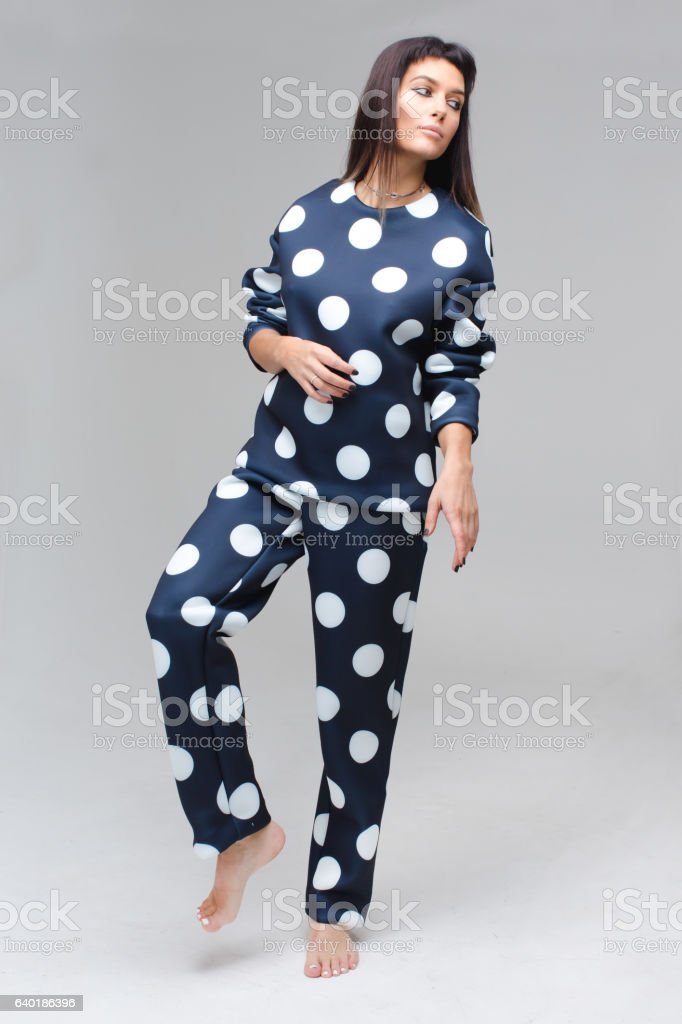 Barefoot model in blue polka dots pajamas staying stock photo