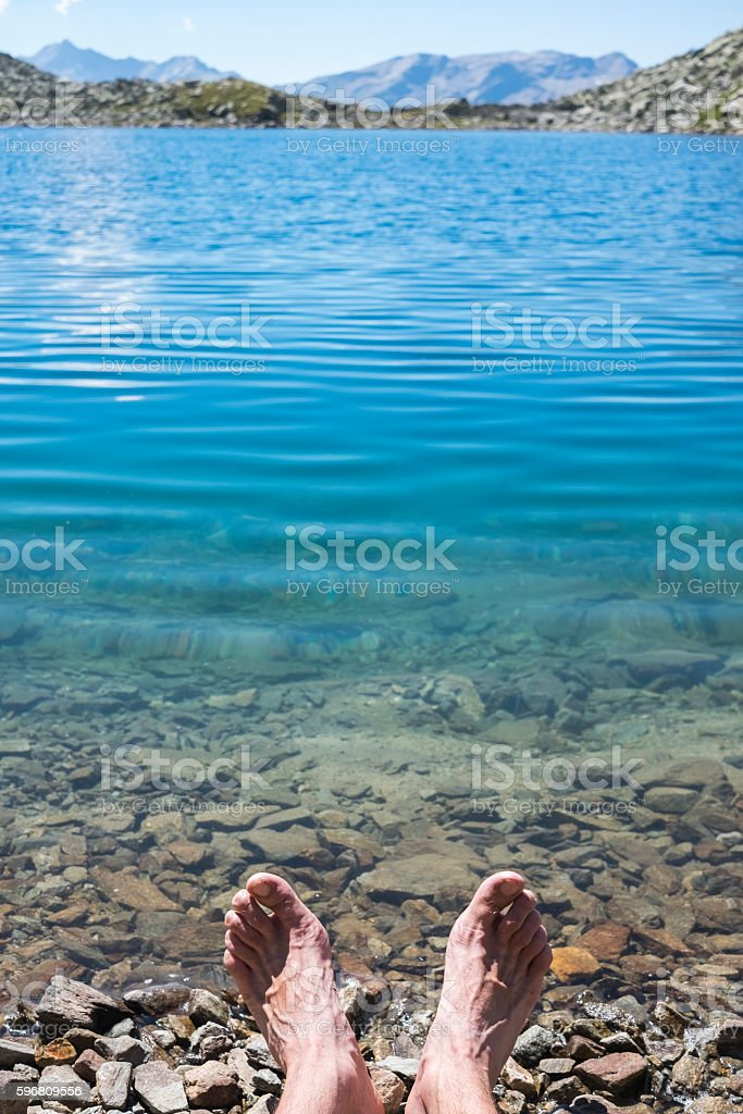 Barefoot near alpine lake stock photo