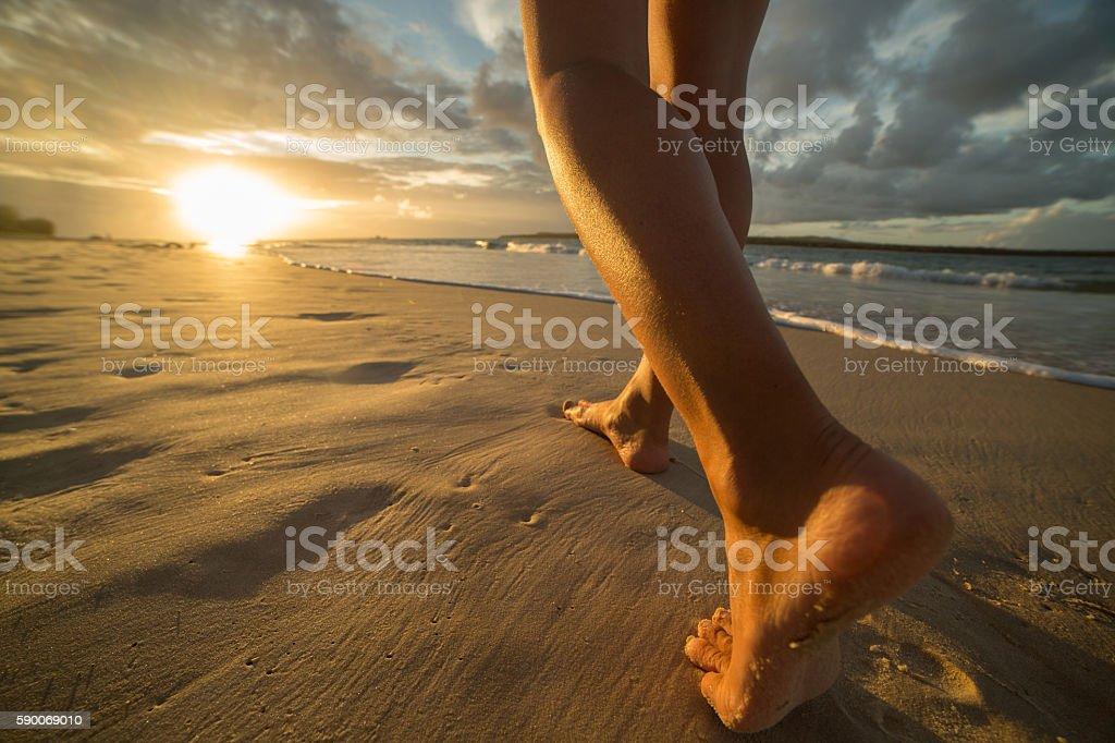 Barefoot on beach walking towards sunlight stock photo