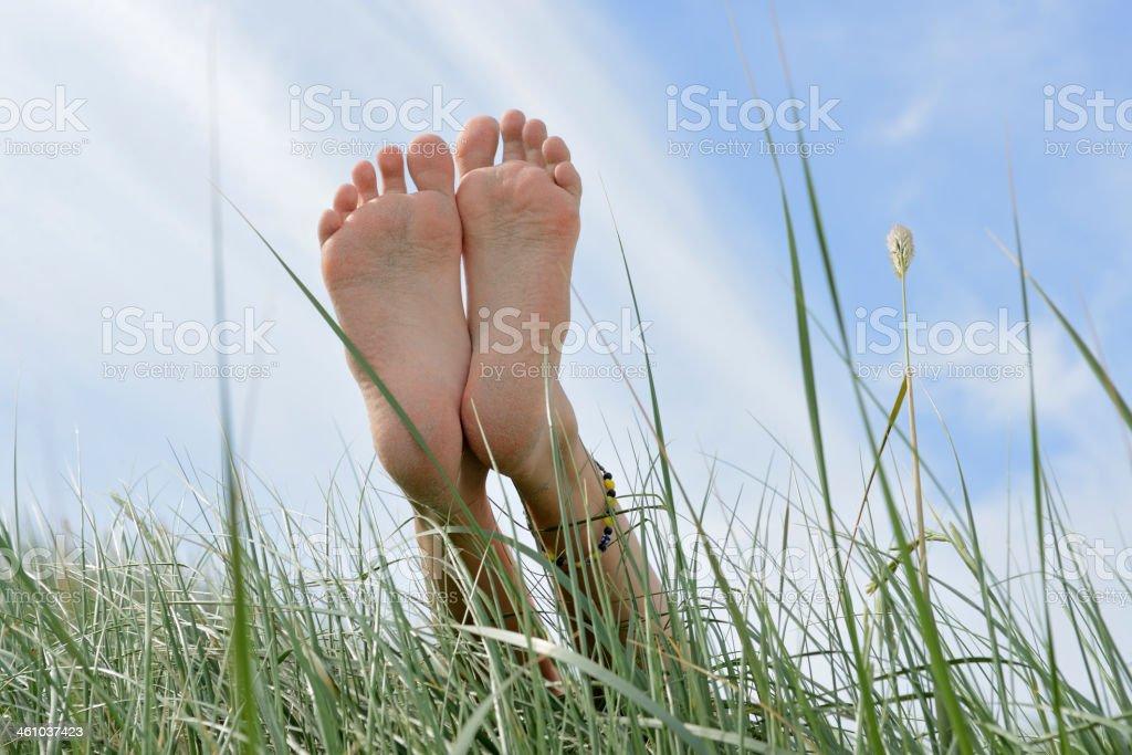 Barefoot on the sand dune under light blue sky stock photo