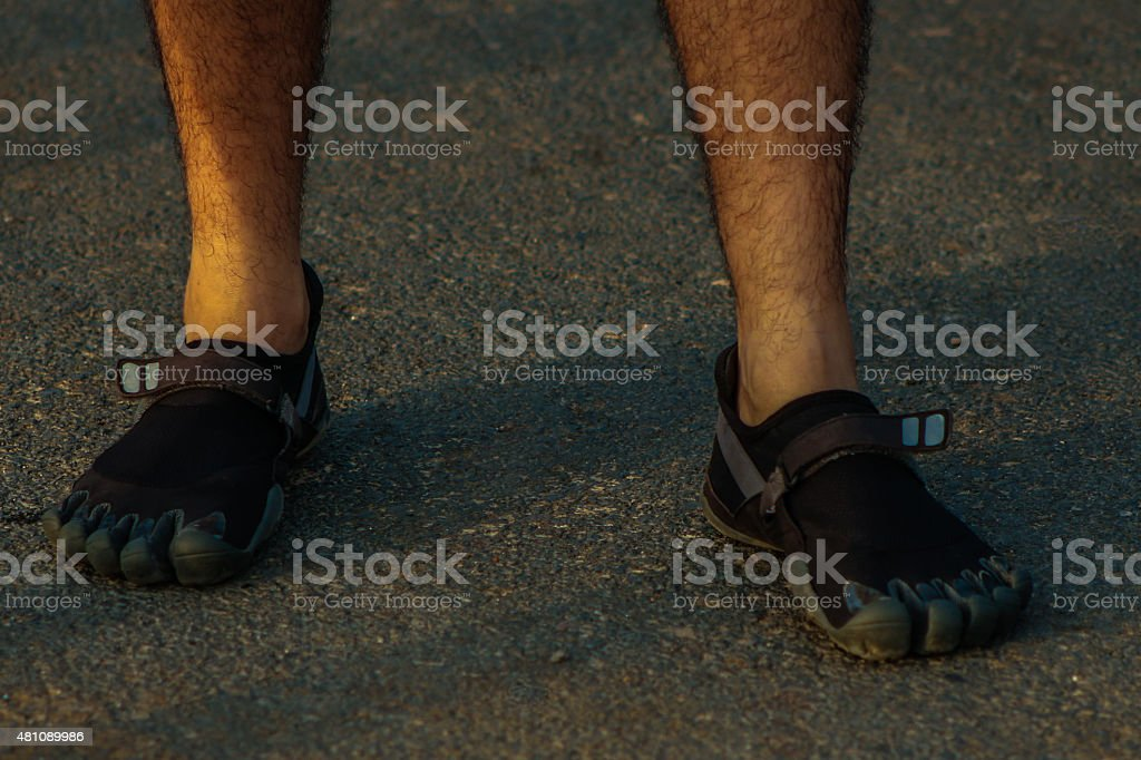 Barefoot runner in black toe shoes also known as fivefingers stock photo