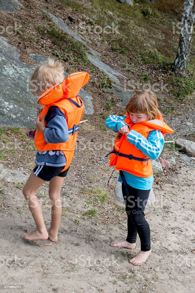 Barefoot small boy and girl with bright orange life jackets royalty-free stock photo