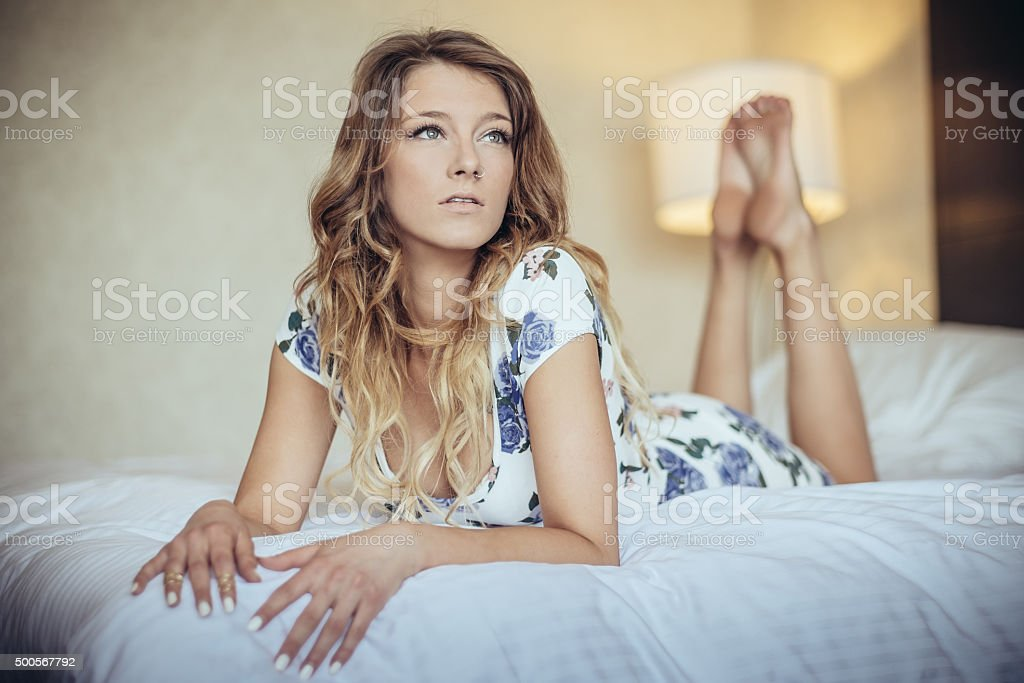 Barefoot woman on the bed stock photo