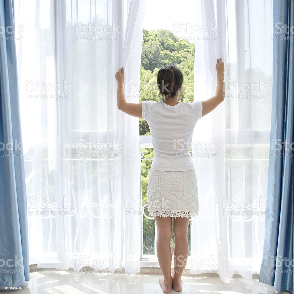 Barefoot woman opening curtains at window royalty-free stock photo
