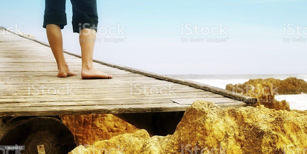 barefoot woman standing on bridge at sea royalty-free stock photo