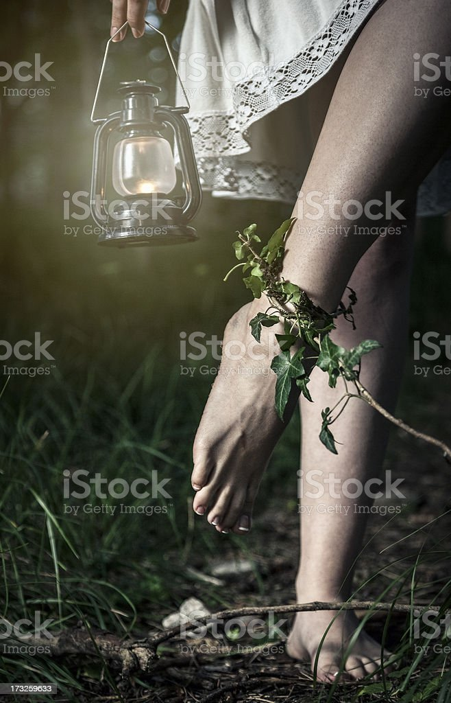 Barefoot woman with lantern trapped in the forest royalty-free stock photo