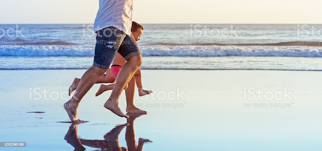 Barefooted legs of family running on beach stock photo