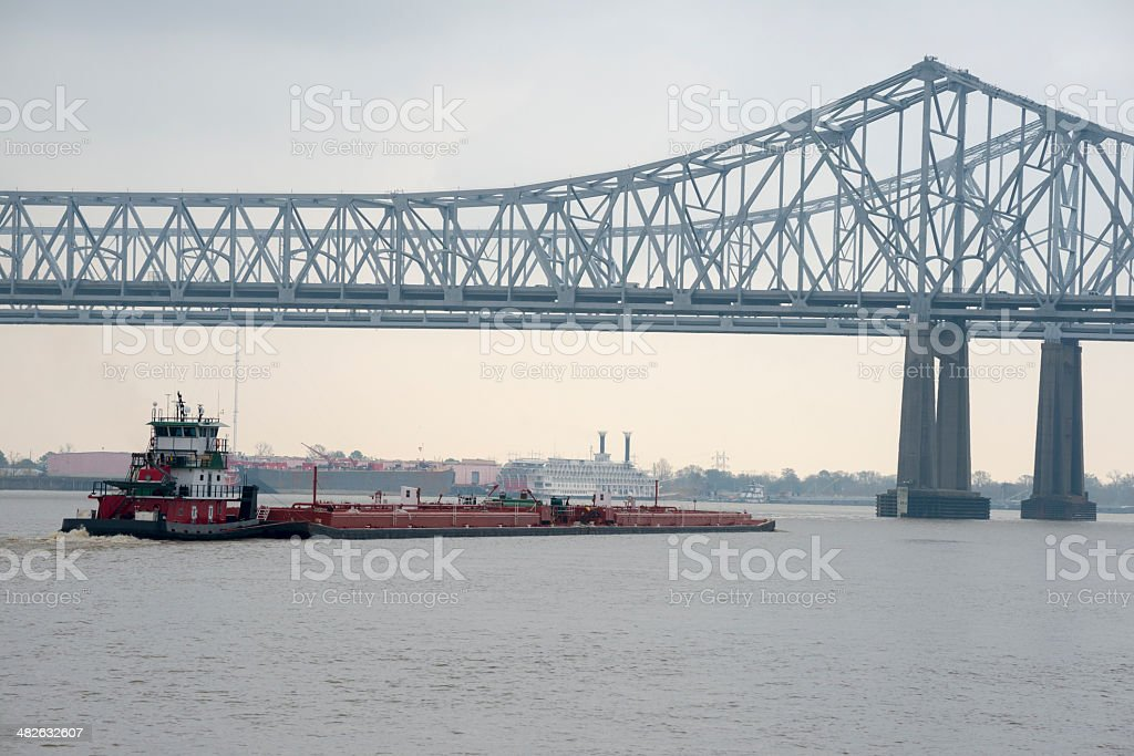 Barge and Crescent City Connection bridge in New Orleans Louisiana stock photo