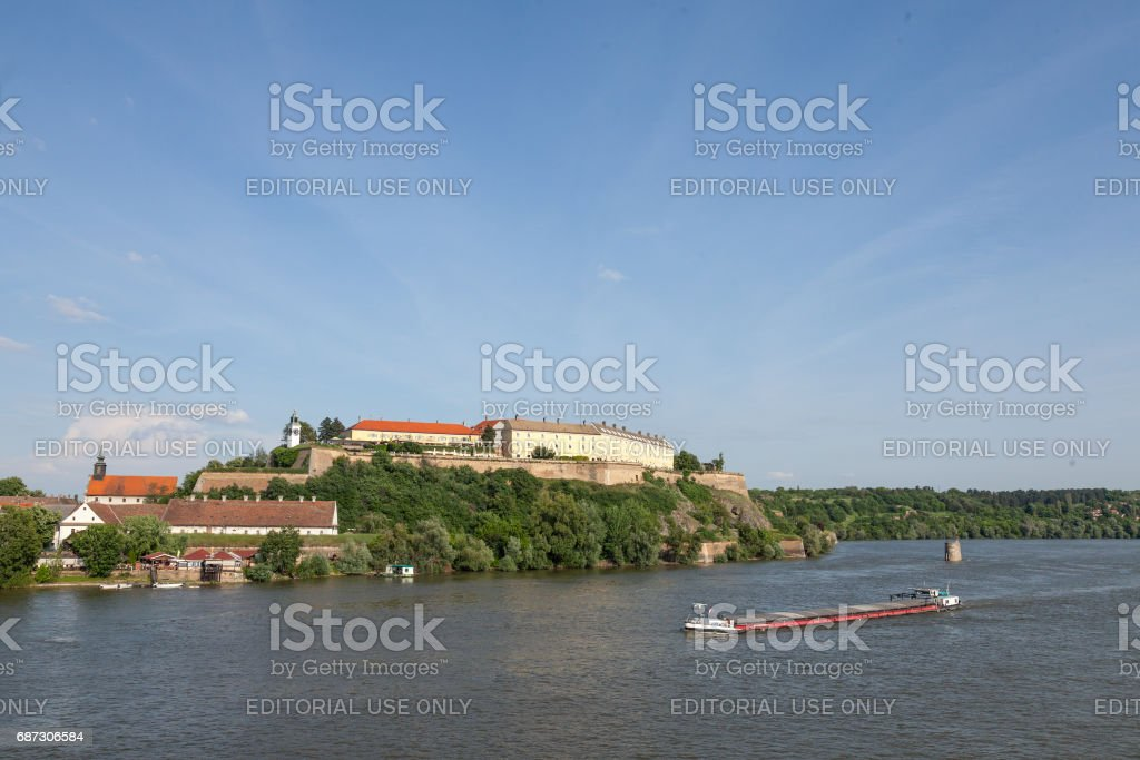 Barge passing in front of Petrovaradin fortress in Novi Sad, Serbia. This castle is one of the symbols of Serbia, Danube river is the main axis of navigation in Europe stock photo