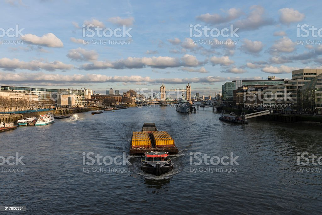 Barge with containers against tower bridge in city of London stock photo