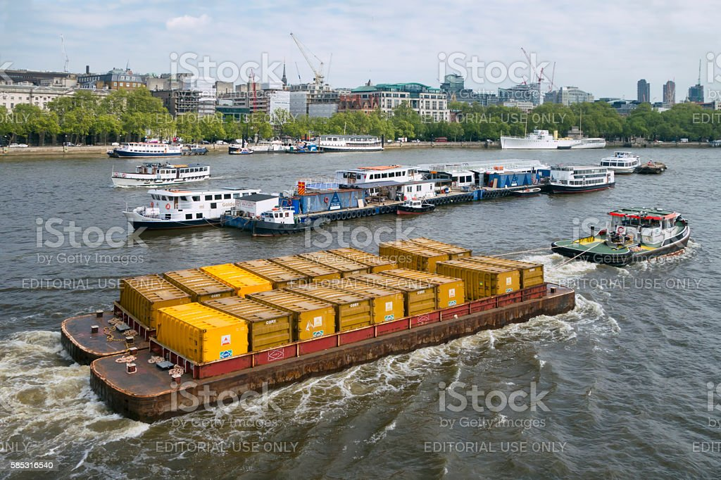 Barges being towed down the River Thames by tug stock photo