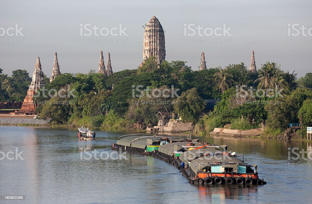 Barges being towed on the Chaoprya River, Ayuthaya, Thailand. stock photo