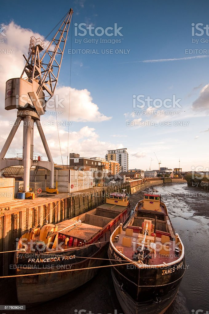 Barges docked at wharf on river under crane stock photo