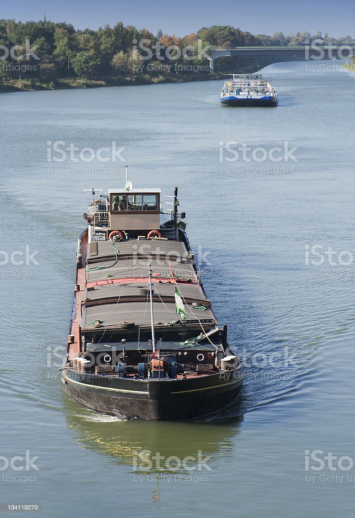 Barges on canal approaching stock photo