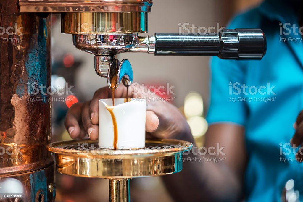 Barista at Espresso Maker Holding Cup While Coffee is Dripping stock photo