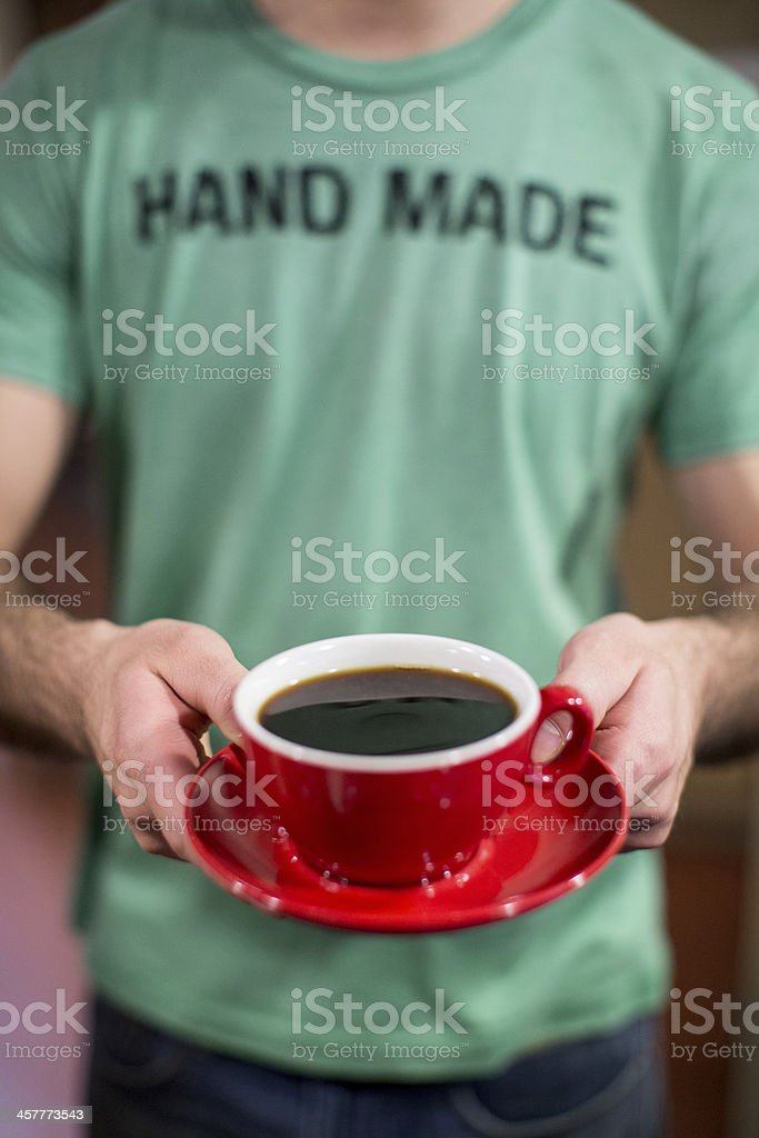 Barista Extending a Cup of Coffee royalty-free stock photo