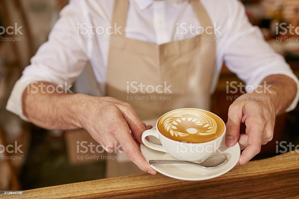Barista giving you a cup of fresh coffee stock photo