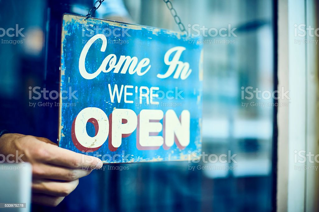 Barista hanging an open sign in restaurant stock photo