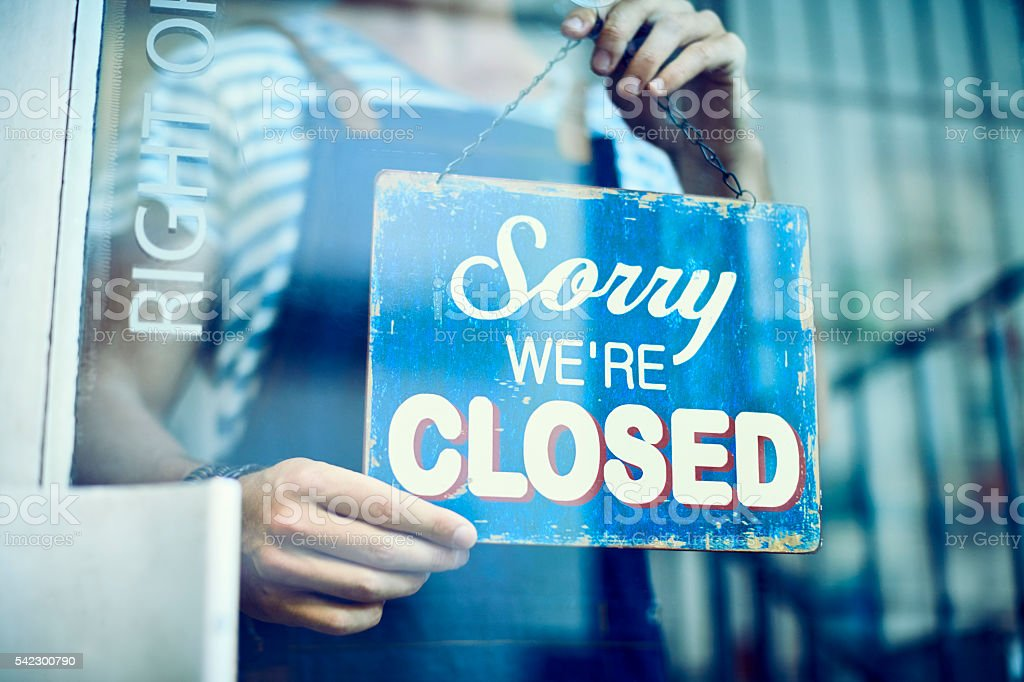 Barista hanging closed sign on window stock photo