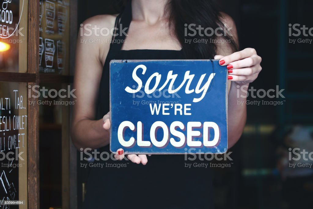 Barista holding an closed sign in coffee shop