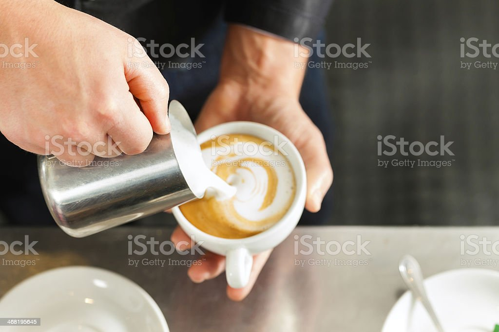 Barista making cappuccino in his coffeeshop stock photo