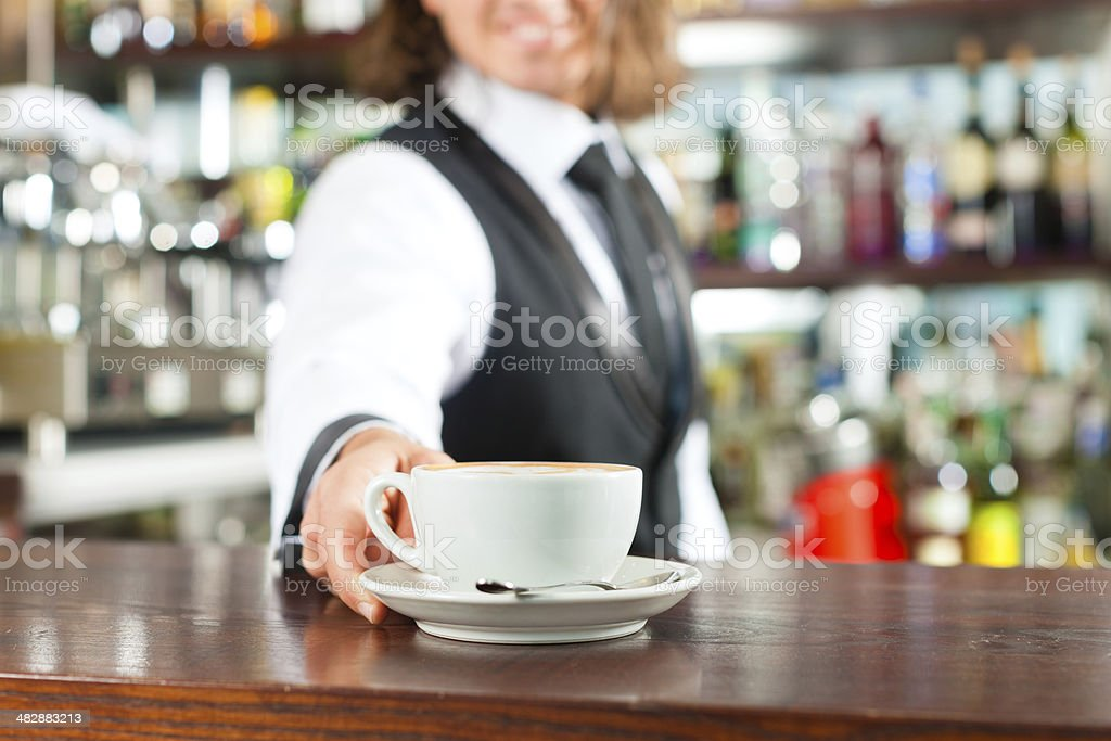 Barista making cappuccino in his coffeeshop royalty-free stock photo