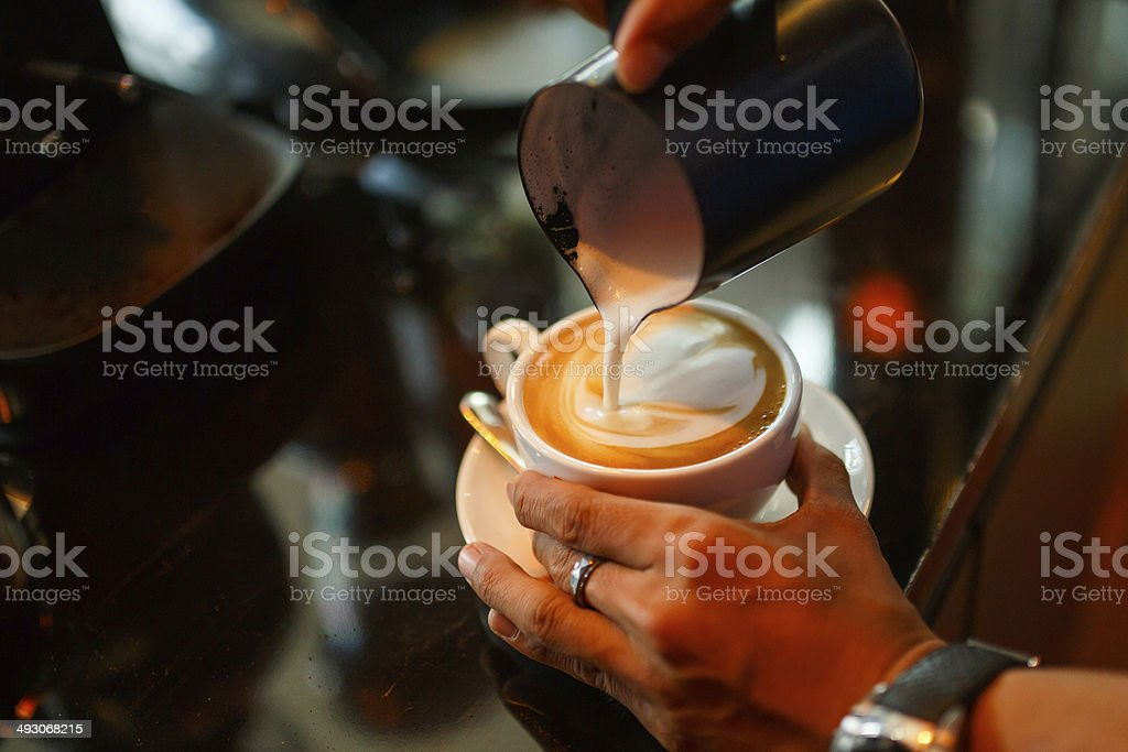 Barista making cappuccino in the coffeeshop stock photo