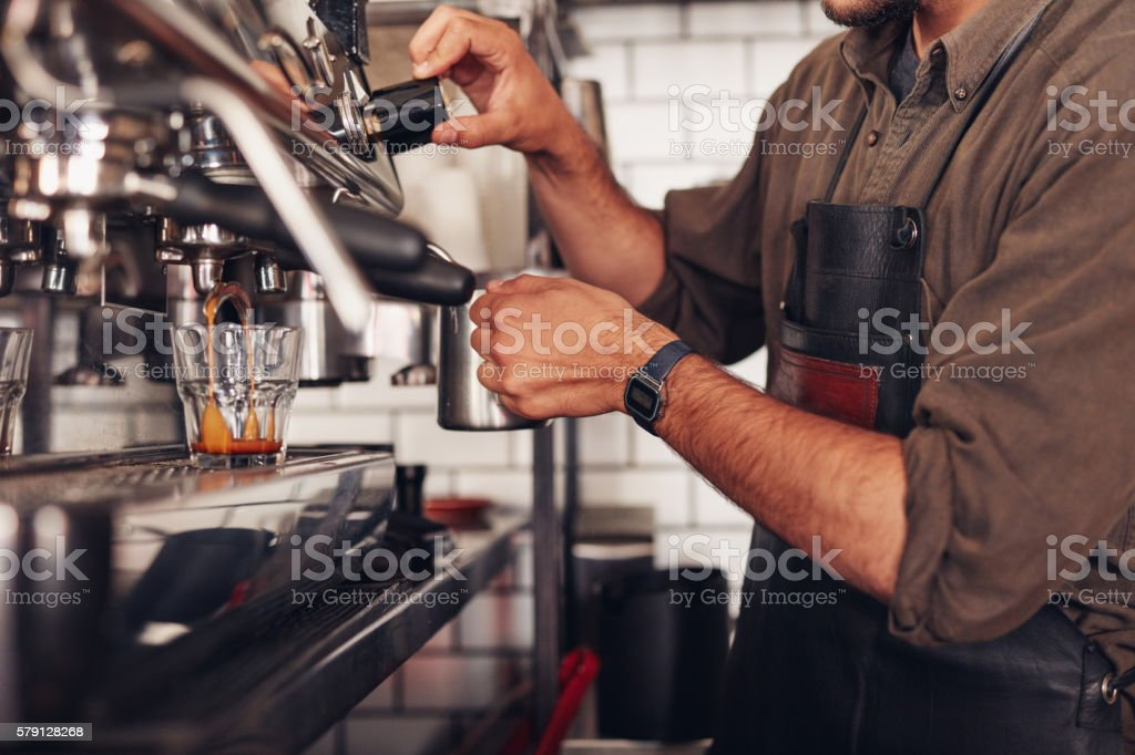 Barista making coffee using a coffee maker stock photo